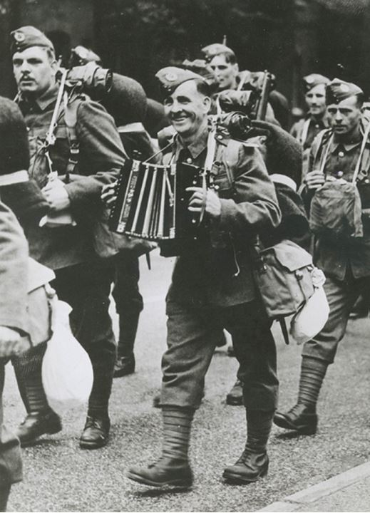 A group of soldiers marching while one plays an accordian