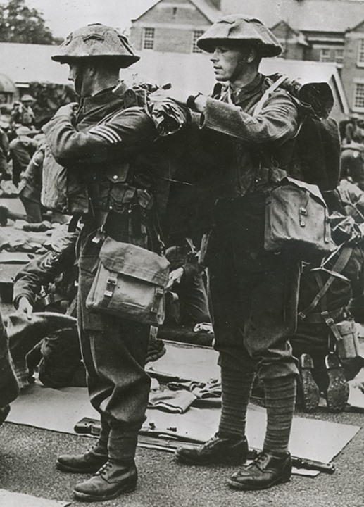 A soldier helps another with his backpack