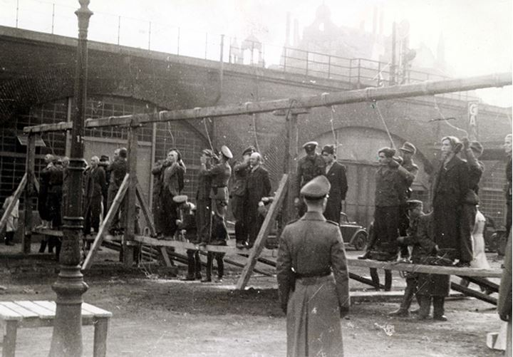 A nazi officer watches as several people are prepared for hanging