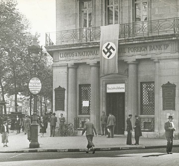 People walking in front of bank with nazi flag hung over it's doorway