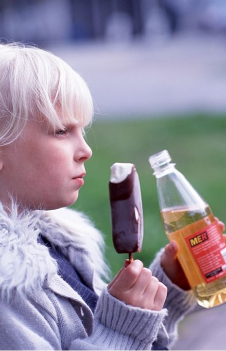 Girl holding an ice-cream and a bottle of juice