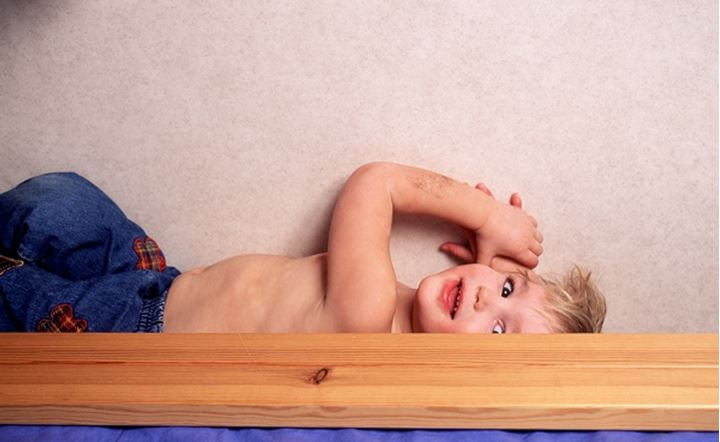 Small boy lying in his bed
