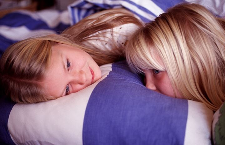 Two girls lying on a pillow