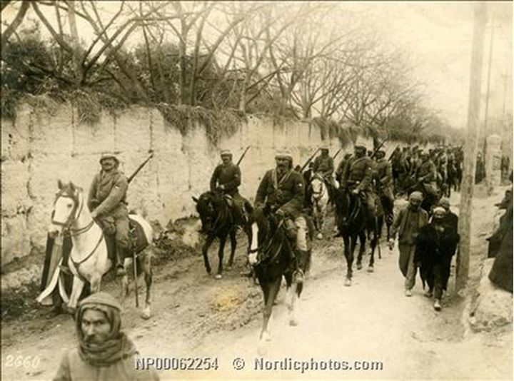 Cavalry soldiers riding in line alongside a wall