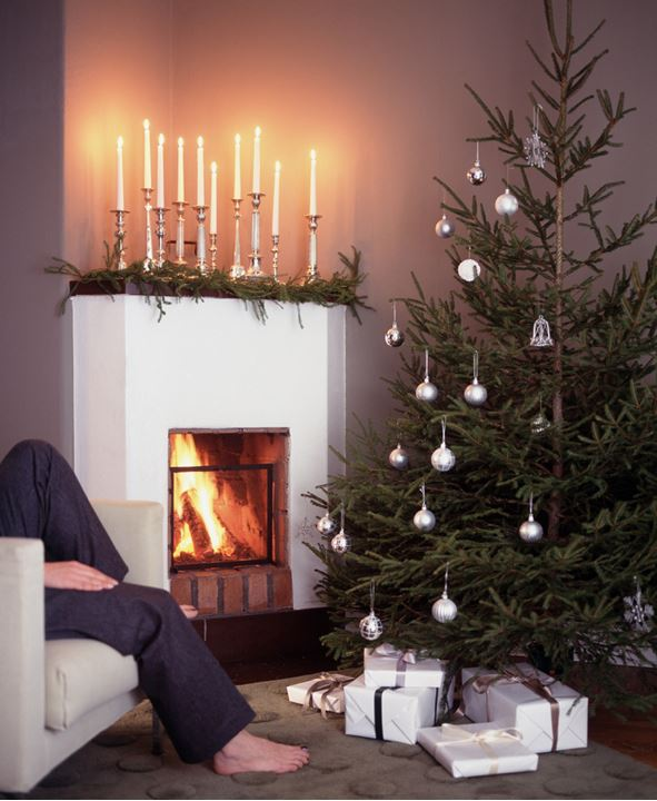 A person sitting in a sofa by a fireside and a christmas tree