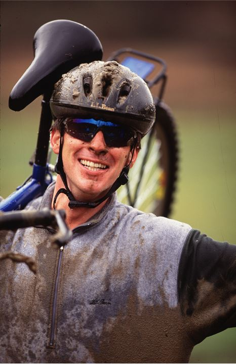 A happy and dirty cyclist with the bike on his shoulder