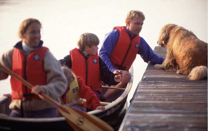 Four people in a boat and a dog on a berth