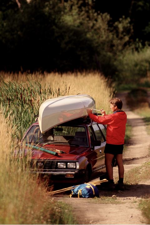 A man binding a boat to a car