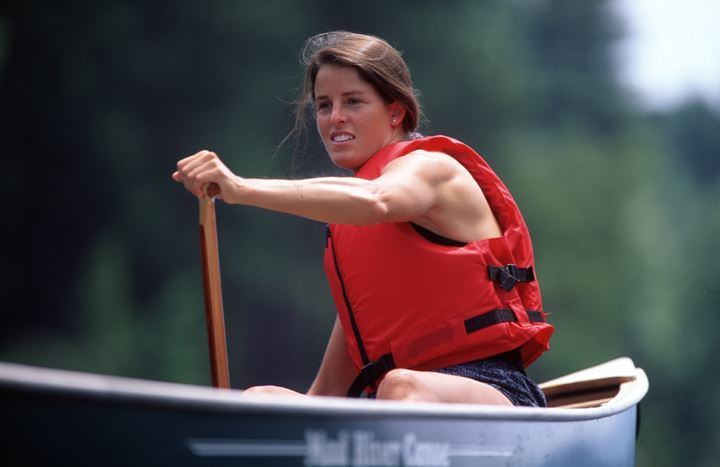 A woman driving a boat in a life jacket