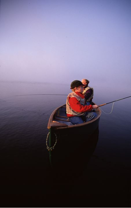 Two fishermen in a boat in haze at dawn