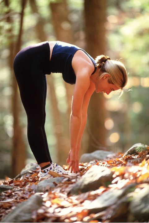 A woman doing exercises in a forest