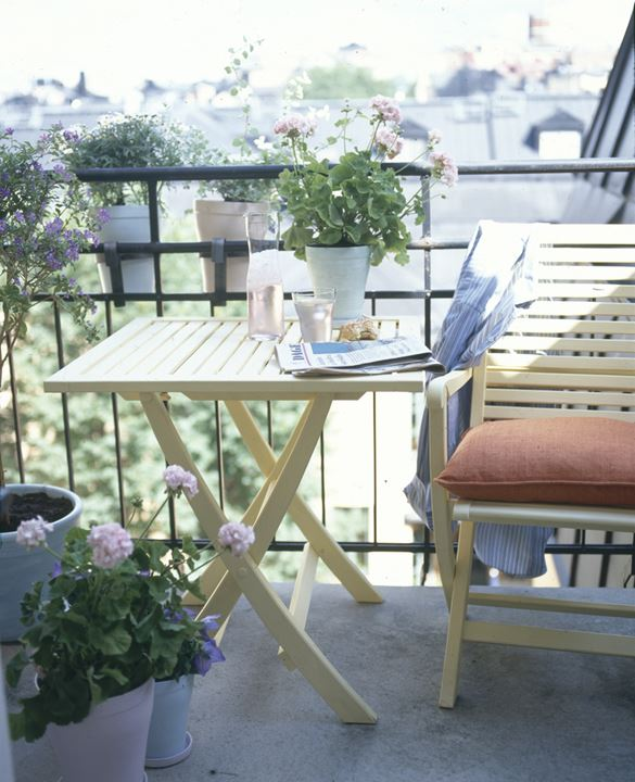 A balcony with a table, a chair and potted plants