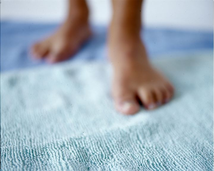 Bare feet stepping on a towel