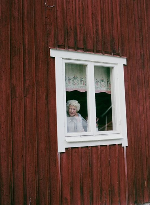 Senior woman looking through the window of her house