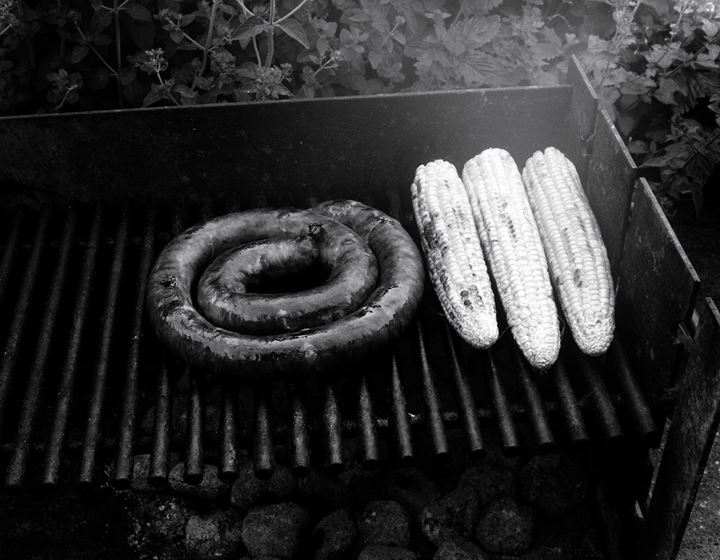 A round sausage and corncobs on a barbeque