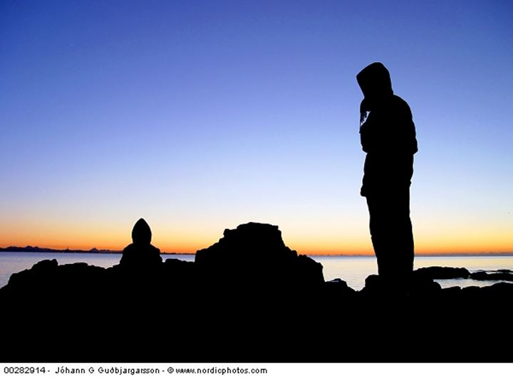 Silhouette of a person by the sea at sunset