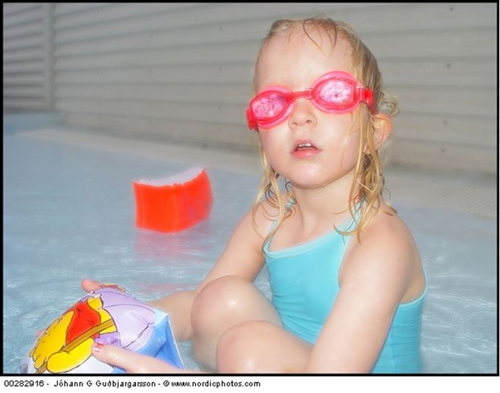 A young girl with goggles and waterwings in a pool