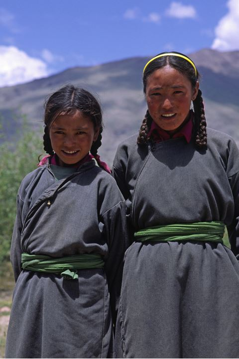 Two smiling girls, dressed in traditional costumes