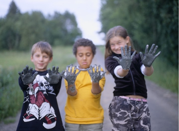 Kids with hands full of mud