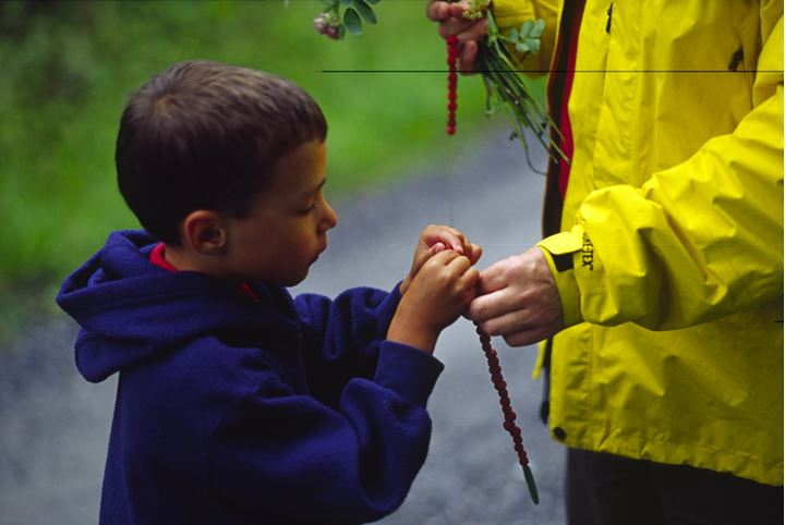 A boy stringing berries on a stick