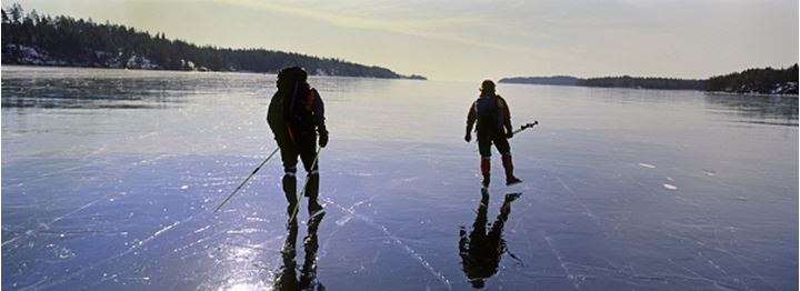 Two people skating on a frozen lake, Sweden