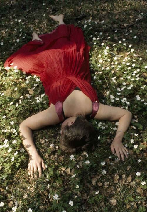 A woman wearing a red dress and lying on grass and white flowers