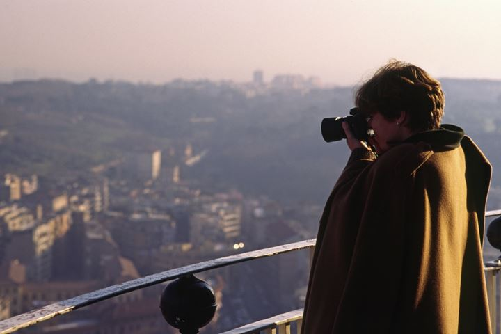 A photographer taking a photograph of a panorama of a city