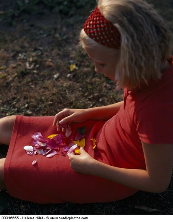 A girl playing with petals