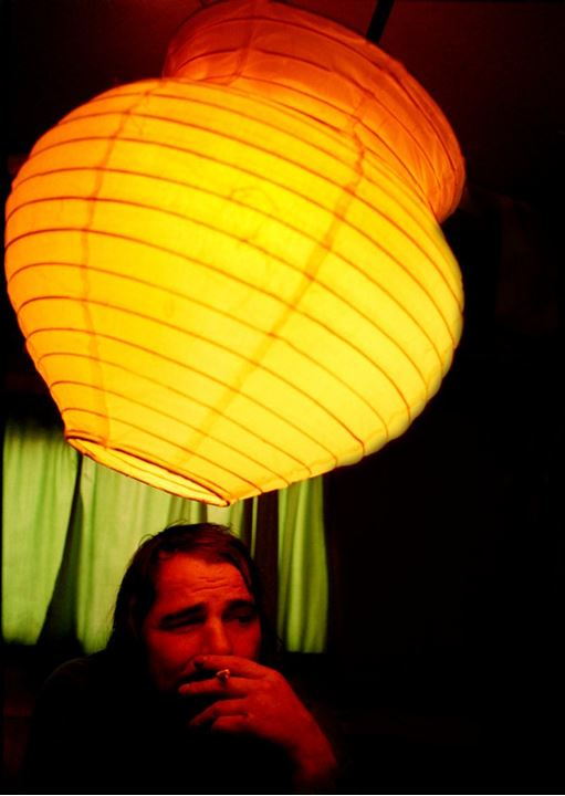 A smoking man in the light of a yellow lamp