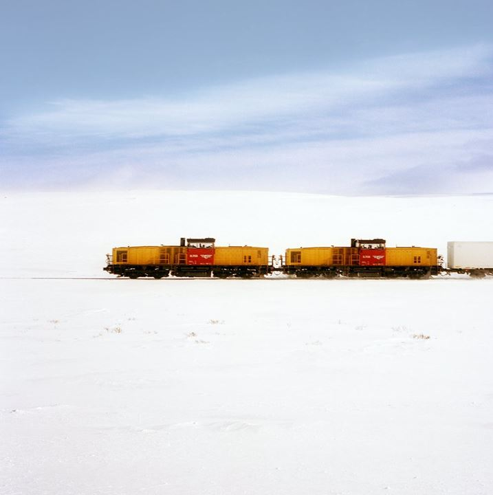 A yellow train travelling through a frozen area