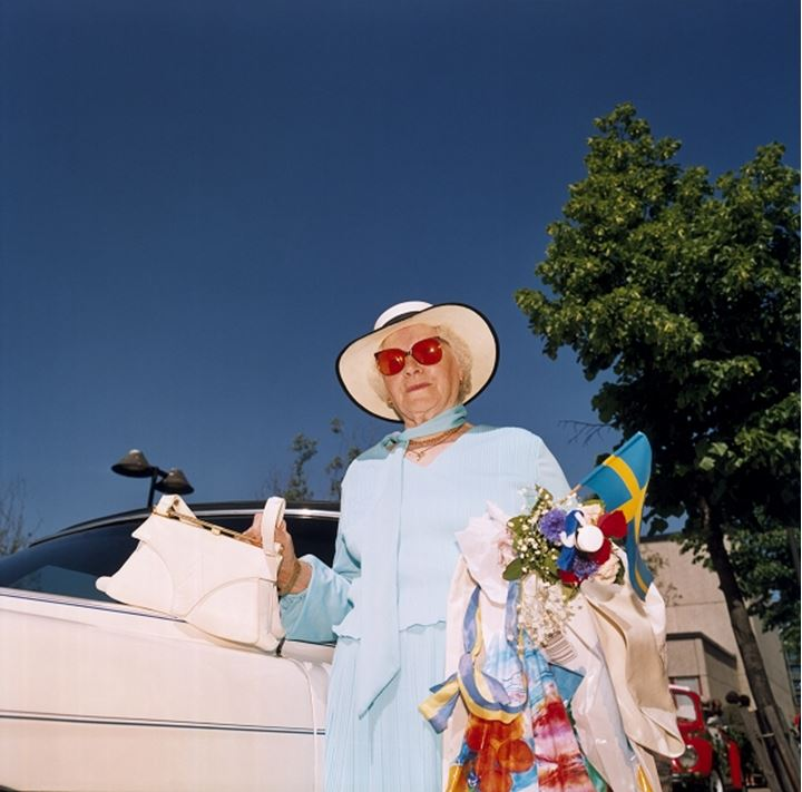 An elderly Swede standing by her car