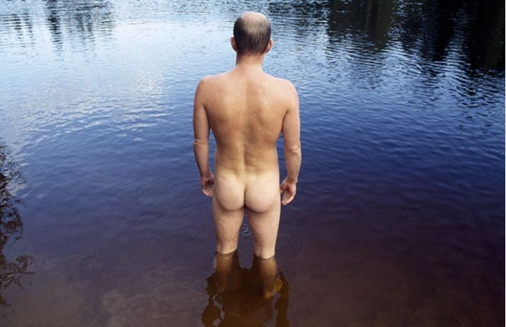 A naked man staring into the water