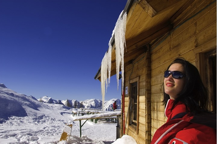 woman sitting in front of hut