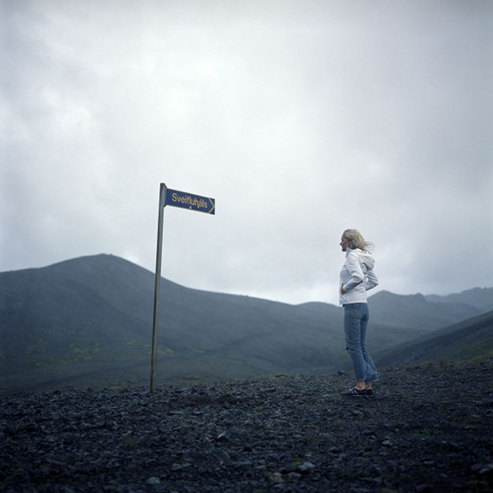 A woman standing by a sign in the highlands in Iceland
