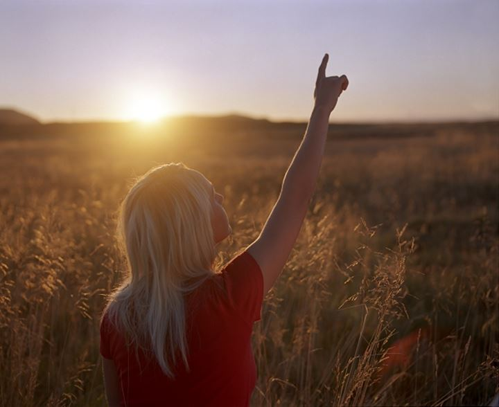 A blonde woman standing in a field, pointing up to the sky