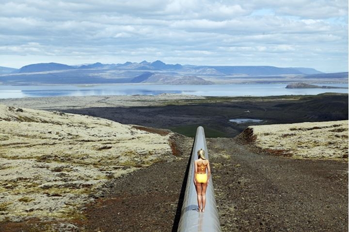 A woman in a bikini, standing upon a hot water pipe, Thingvallavatn, Iceland