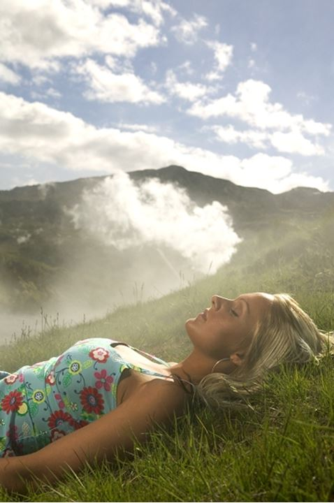 A woman resting in grass, steam in background, Nesjavellir, Iceland