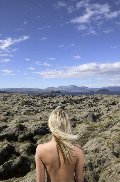 A naked woman standing in a mossy lava field, Iceland