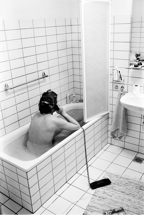 A woman talking on the phone in her bath