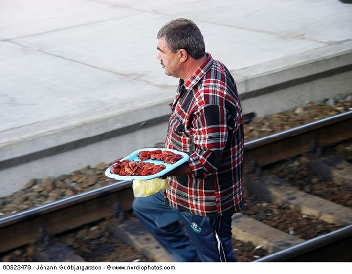 A man carrying crayfishes on a tray crossing a railway