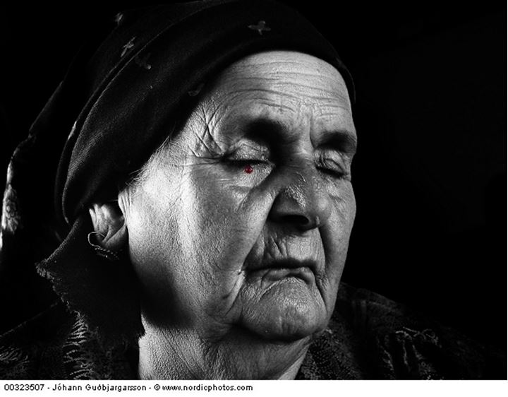 An elderly woman with closed eyes