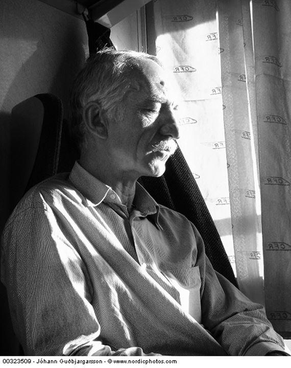 A middle aged man sleeping in a compartment