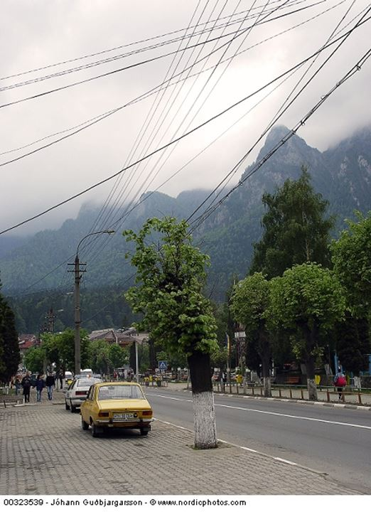 Wires over a street against misty mountains