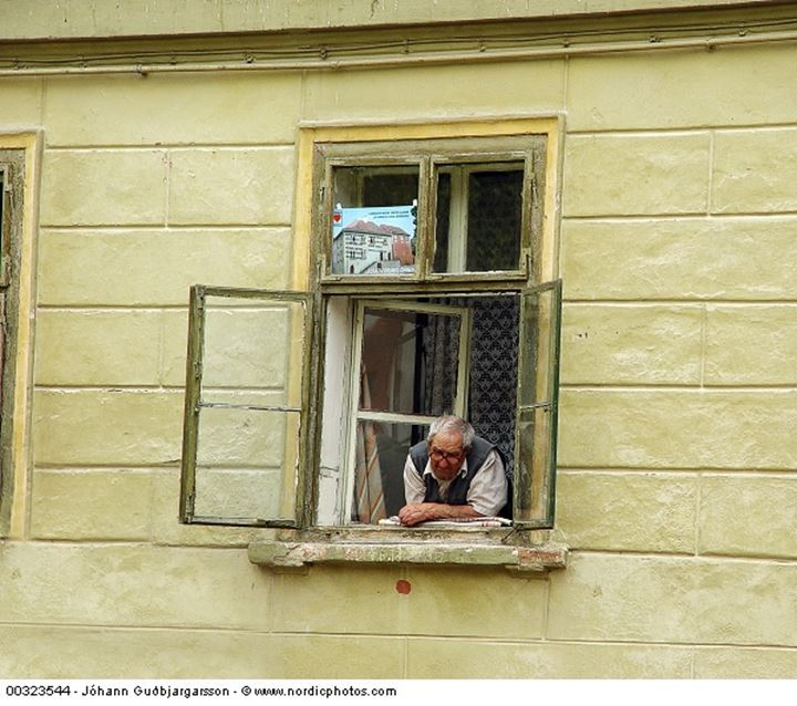 An elderly man looking out of a window