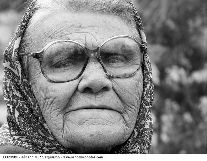 An elderly woman wearing spectacles and a kerchief
