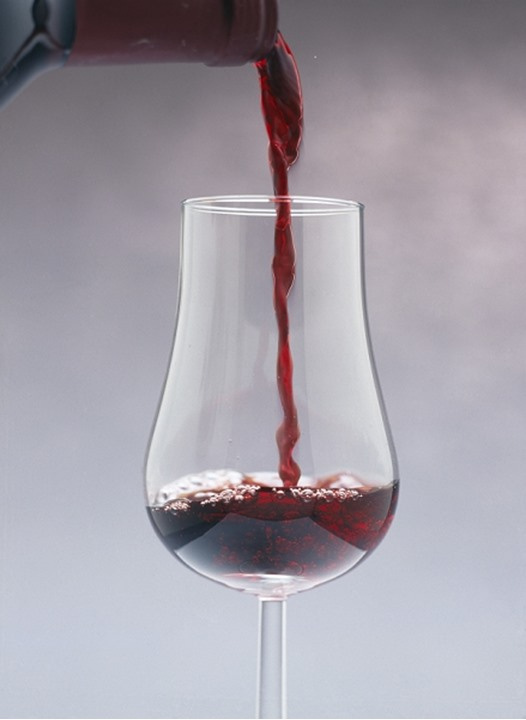Red wine poured into a glass.
