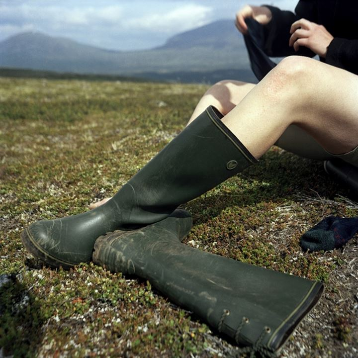 Low section view of a person sitting in a grassy field, Jamtland, Sweden