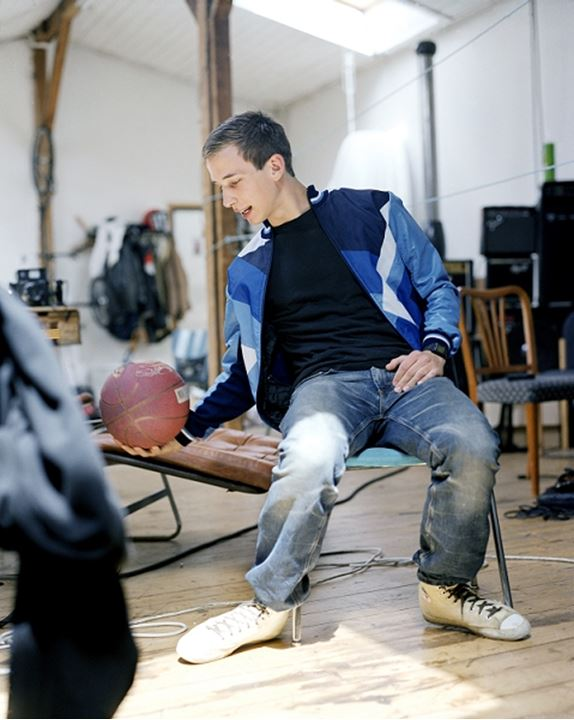 A young man playing with a basket ball in his home