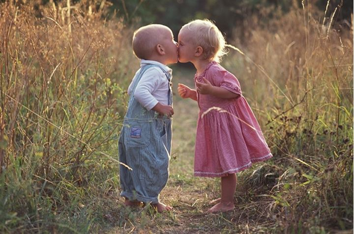 Boy and girl, 1,5 years old, kisses in a meadow, Gotland