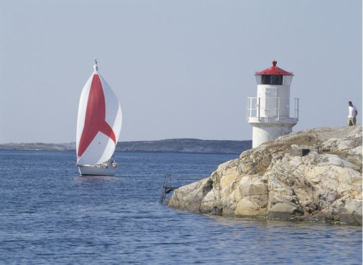 A sailboat sailing by a small beacon, Sweden